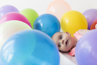 Caucasian baby girl laying in balloons
