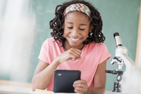Black student using digital tablet in science class