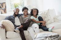 Black family smiling on sofa