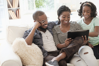 Black family using digital tablet on sofa