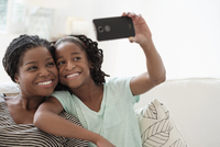 Black mother and daughter taking selfie