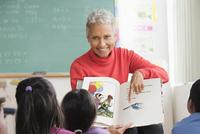Mixed race teacher reading to class