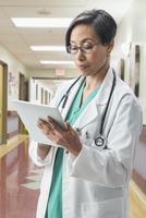 Black doctor using digital tablet in hospital