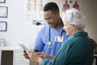 Nurse and patient using digital tablet in clinic