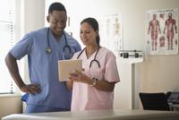Nurses using digital tablet in clinic