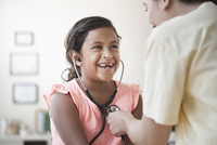 Nurse helping patient use stethoscope