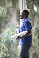 Black businessman holding blueprints in office