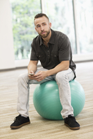 Caucasian businessman sitting on exercise ball