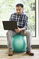 Mixed race businessman using laptop on exercise ball