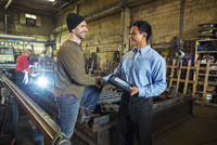 Worker and businessman shaking hands in factory