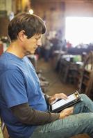 Caucasian worker using digital tablet in factory