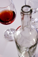 Close up of wine glass and empty bottle