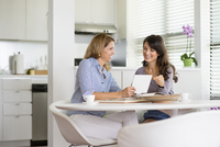Caucasian women using digital tablet in kitchen