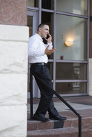 Caucasian businessman talking on cell phone outdoors