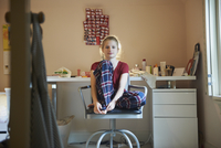 Caucasian girl sitting in bedroom