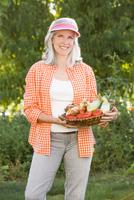 Caucasian woman holding basket of vegetables in garden