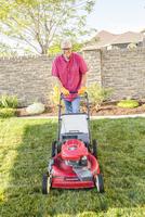Caucasian man mowing lawn in backyard