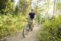 Caucasian father and children riding mountain bikes