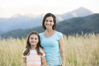 Caucasian mother and daughter smiling in field