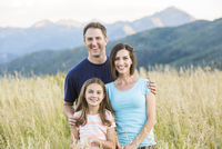 Caucasian family smiling in field
