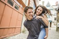 Caucasian man carrying girlfriend piggyback in village