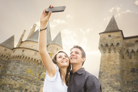Caucasian couple taking selfie at castle