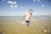 Caucasian boy splashing in waves on beach