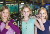 Caucasian girls playing with snake in pet store