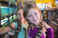 Caucasian girls playing with snakes in pet store