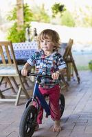 Caucasian boy riding bicycle on patio