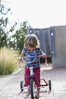 Caucasian boy riding tricycle in backyard