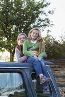 Caucasian mother and daughter hugging on truck roof
