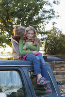 Caucasian mother hugging daughter on roof of truck