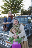 Three generations of Caucasian women sitting on truck