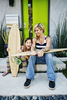 Caucasian mother and daughter with skateboards