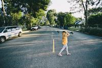 Caucasian girl crossing suburban street