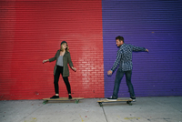 Caucasian couple riding skateboards on sidewalk