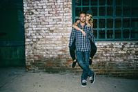Caucasian man carrying girlfriend piggyback outdoors