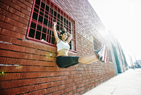Mixed race woman doing pull-ups on window grate