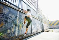 Mixed race woman climbing gate