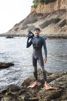 Hispanic diver wearing wetsuit on beach