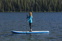 Caucasian woman standing on paddle board in river