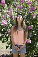 Asian woman standing under flowers