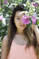 Asian woman hiding behind flower