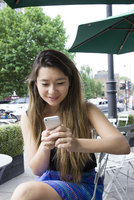 Asian woman using cell phone outdoors