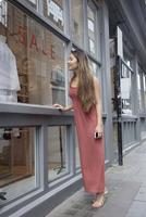 Asian woman window shopping outside store