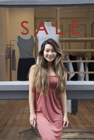 Asian woman standing outside store