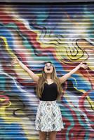 Asian woman cheering near graffiti wall