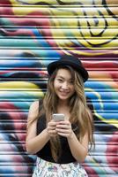 Asian woman using cell phone near graffiti wall