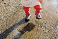 Caucasian baby girl walking in puddle